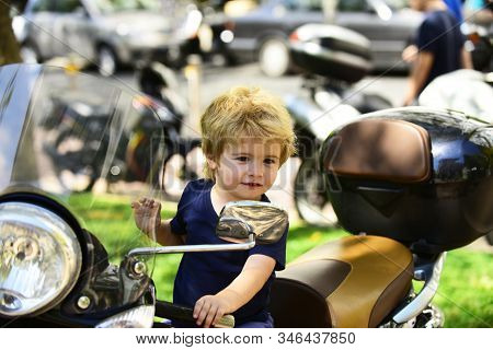 Small Kid Sits On Motorbike And Smiles. Sincere Emotions From Little Boy. Motorbikes On Street Backg