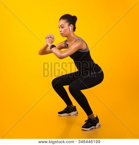 Afro Lady In Fitwear Exercising Doing Deep Squat Working Out On Yellow Background. Studio Shot