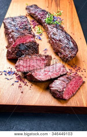 Barbecue dry aged venison tenderloin fillet steak natural with herbs and salt offered as closeup modern design wooden board