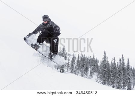 Amateur Snowboarder Is Jumping From Small Kicker In The Winter Forest.