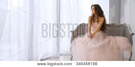 beautiful young caucasian girl sitting near the window in pink fashion dress indoors at home