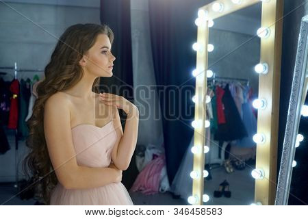 portrait of attractive young  caucasian woman girl in pink dress looking at mirror indoors