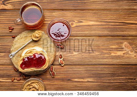 Toast Sandwich With Peanut Butter. Spoon And Jar Of Peanut Butter, Jam, Cup Of Tea And Peanuts For C