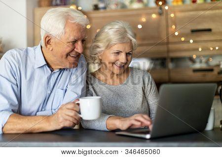 Senior couple using laptop in their kitchen