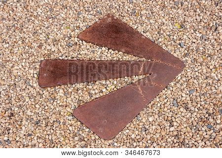 Richmond, Tasmania, Australia - December 13, 2009: Closeup Of Heavy Rusty Metal Arrow Set In Gravel