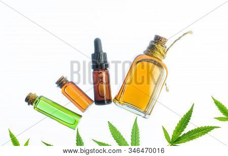 Glass Bottles With Cbd Oil And Thc Tincture And Hemp Leaves On White Background. Flat Lay Cosmetics