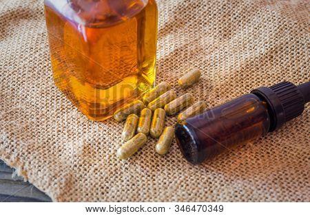 Glass Bottle With Cannabis Cbd Thc Oils And Cbd Pills On Hemp Cloth, Medical Marijuana Concept