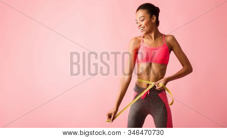 Fitness And Weight Loss. Black Girl In Fitwear Measuring Thin Waist With Tape Posing Over Pink Backg