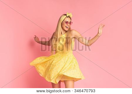 Enjoying Life. Happy Young Blonde Woman In Yellow Dress And Heart Glasses Dancing On Pink Studio Bac