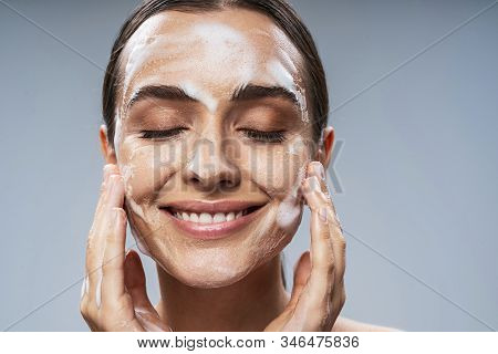 Amazing Girl Washing Her Face With Foam Against Light Background