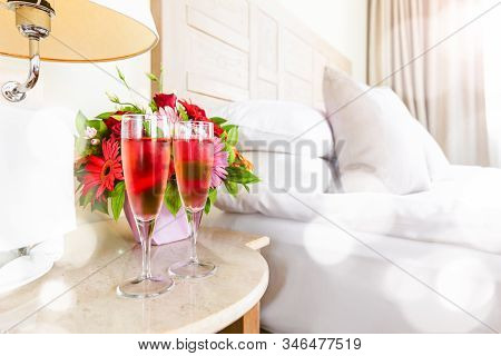 Two Glasses Of Rose Champagne With Light Festive Bokeh In The Upscale Hotel Room. Dating, Romance, H
