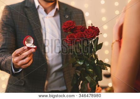 Valentines Day Proposal. Romantic Man With Engagement Ring And Roses Flowers Asking Girlfriend To Ma