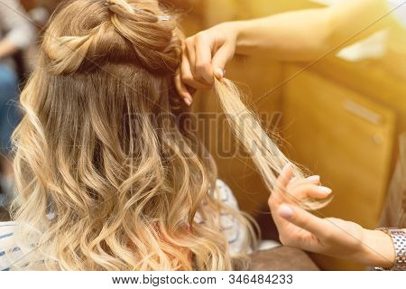 The Hairdresser Creates Curls And Wavy Hair In The Blonde. Hands Of The Hairdresser Curls Curls At T