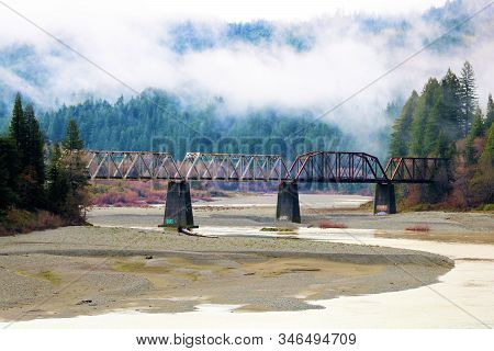 Historical Railroad Bridge With Rusty Trestles Over The Eel River Surrounded By Lush Forests And Mou