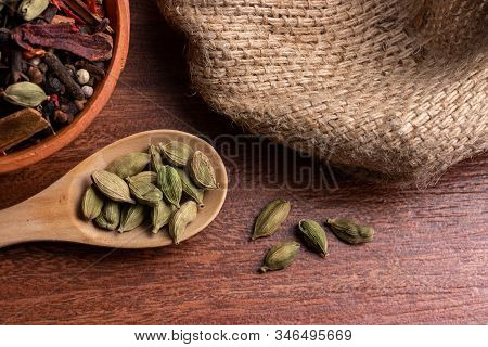 Close-up Of Dried Cardamom Pods In Spoon On Wood Background, Indian Spice For Cooking
