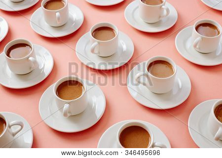White cups filled with coffee and milk, arranged on pink background.