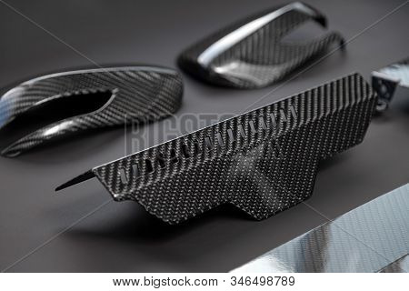 A Close-up On A Car Exterior Elements Made From Carbon Fiber Of Interwoven Black And Gray Color From
