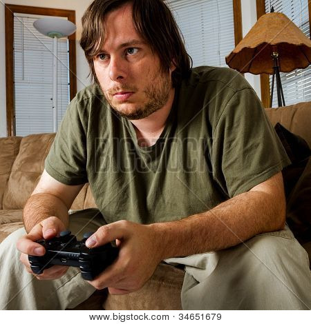 Middle Aged Man Playing Games On The Couch