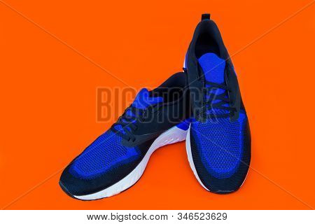 Pair Of Blue Sport Shoes On Orange Background. Sport Shoes Isolated. File Contains A Clipping Path.