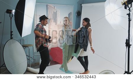 Backstage Of The Photo Shoot: Photographer With Assistant Choosing Clothes For Models Photo Shooting