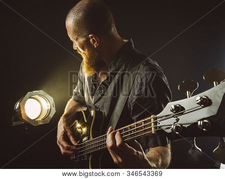 Photo Of A Bearded Man Playing Electric Guitar On Stage In Front Of Spotlights.