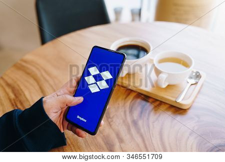 Chiang Mai, Thailand - Jan.18,2020: Man Holding Xiaomi Mi Mix 3 With Dropbox On Wooden Table At Coff