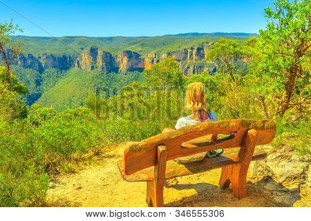 Caucasian Tourist Woman Sitting On Wooden Bench, Looking Panoramic Views Along Anvil Rock Trail Near