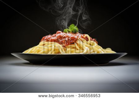 Spaghetti Italian Pasta Served On Black Plate With Tomato Sauce And Parsley In The Restaurant Italia