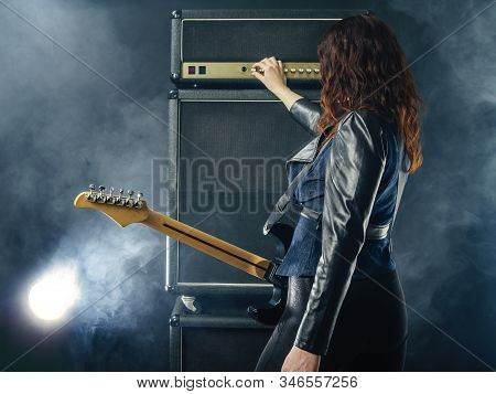 Redhead Woman With Electric Guitar Adjusting Her Amplifier While On Stage.