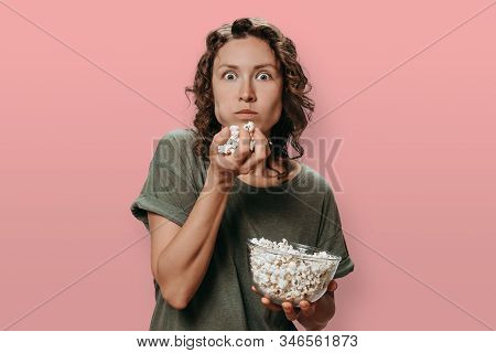 Portrait Of Interested Young Woman With Curly Hair Eating Popcorn, Exated With Movie Or Tv Shows. Pr