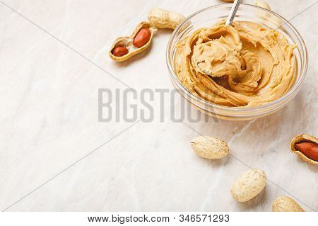 Peanut Butter In Glass Plate With Peanuts In Shell, Peeled Peanuts, Spoon With Peanut Butter. Creamy