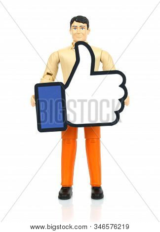 Kiev, Ukraine - November 27, 2019: Toy Man Holds Facebook Like Paper Logo. Facebook Is A Well-known