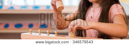 Panoramic Shot Of Child Playing With Wooden Game At Table In Montessori School, Cropped View