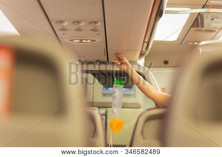 Air Hostess Is Showing How To Use Oxygen Mask Before Taking Off.