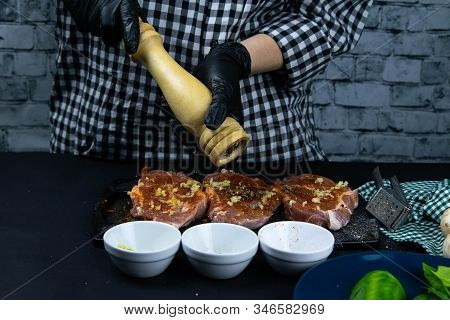 A Chef In Black Gloves Sprinkled With Pepper From Hand Pepper A Raw Tenderloin. Fresh Raw Pork Tende