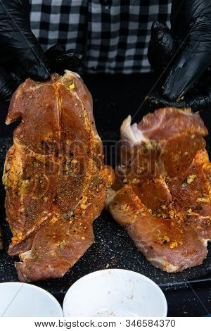 A Chef In Black Gloves Prepares A Raw Tenderloin. Fresh Raw Pork Tenderloin On A Wooden Cutting Boar