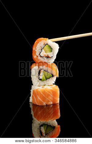 Chopstick Near Delicious Philadelphia Sushi With Avocado, Creamy Cheese, Salmon And Masago Caviar Is