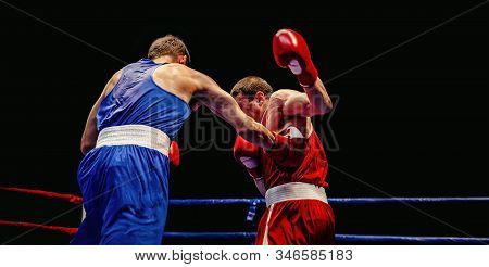 Boxer Blow To Body Opponent During Boxing Match On Black Background