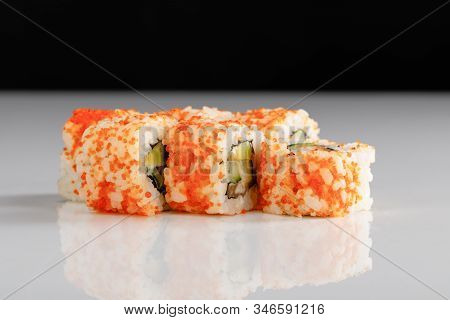 Delicious California Roll With Avocado, Salmon And Masago Caviar On White Surface Isolated On Black