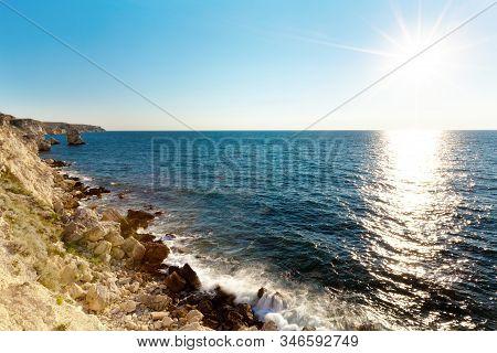 Seascape Of Still Blue Sea Waters Shore, Rocky Coastline And Bright Sun Over Water Horizon On Summer