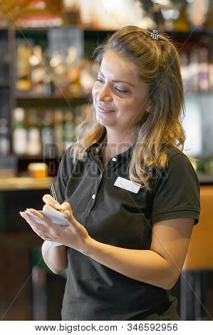 Waitress With A Notebook Takes An Order. Waitress Taking Order On A Notebook In Pub. Waiter Writing