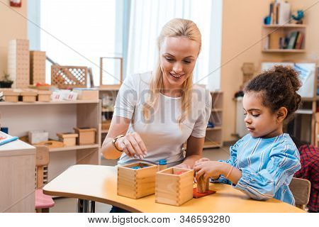 Smiling Teacher Playing Wooden Game With Child During Lesson In Montessori School