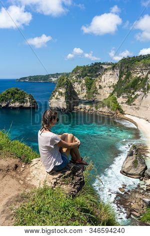 Young Woman Sitting On The Cliff And Enjoying The View