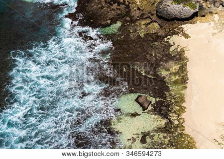Epic Aerial View Of Blue Ocean Waves Crashing Into Rocky Coast