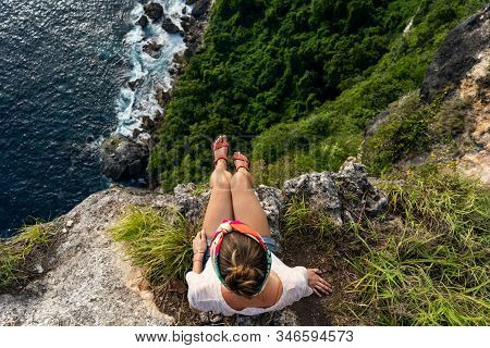 Girl Sitting On The Cliff And Enjoing View On Ocean