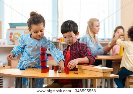 Selective Focus Of Kids Folding Educational Game With Teacher And Children At Background In Montesso