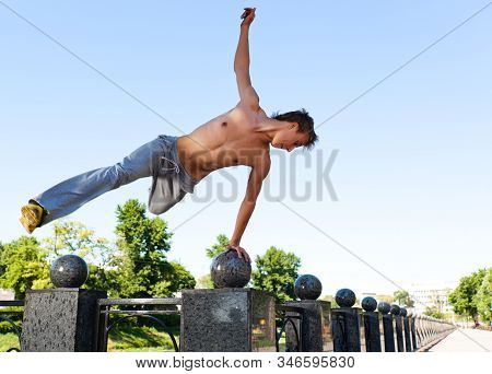 Young Man In Sportswear Jumping And Practicing Parkour Outside On Marble Fence On Clear Summer Day W