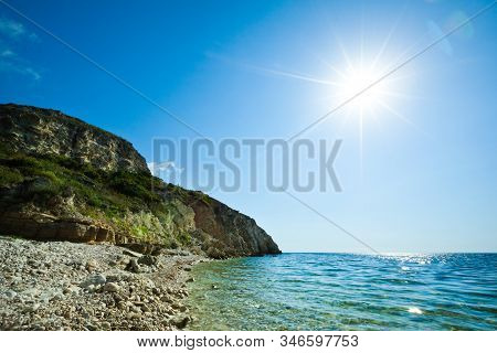 Seascape Of Still Blue Sea Waters Shore, Stone Beach And Green Rock Behind On Summer Clear Day With