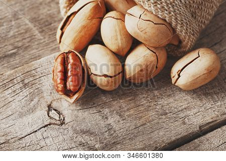 Pecans Spill Out Of A Bag On A Wooden Table, Close-up. Peeled, In A Shell. Low Contrast