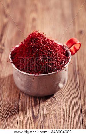 saffron threads background with vintage mug, truly color, huge amount of spice , soft focus